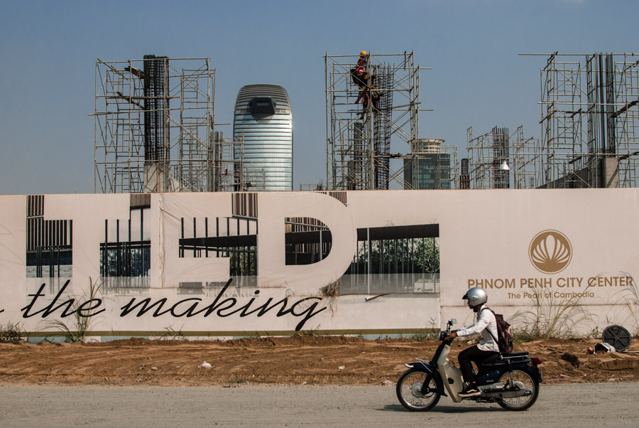 A motorbike drives past a new housing development under construction in Phnom Penh's Boeung Kak area.